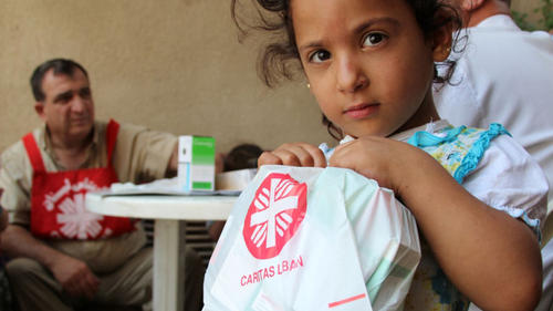 A Syrian refugee child holds free medicine given to her by a mobile clinic run by our partner Caritas Lebanon