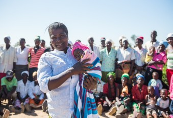 Marian stands with other members of Chinyama community veg garden with her two-month-old baby girl Talent. Zimbabwe